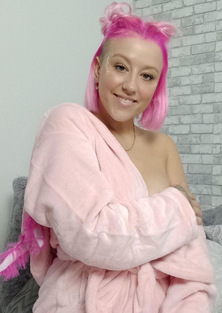Nika-Venus mit pinken Haaren halbnackt am posen